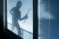 Burglar wearing a balaclava looking through house window